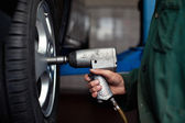 Auto mechanic changing wheel — Stockfoto