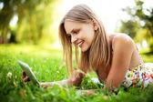 Młoda kobieta za pomocą tabletu odkryty — Zdjęcie stockowe
