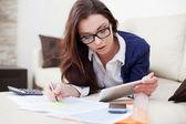 Jonge vrouw werken vanuit huis met behulp van haar digitale tablet pc — Stockfoto