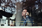 Businessman talking on phone in coffee shop — Stock Photo