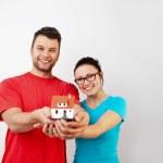 pareja joven sosteniendo miniatre casa — Foto de Stock