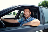 Young man in car smiling — Stock Photo