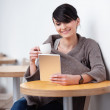 Young woman sitting in the restaurant with digital tablet — Stock Photo #25735627