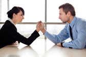 Businessman and businesswoman arm wrestling — Stock Photo