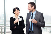 Businessman and businesswoman drinking coffee — Foto de Stock