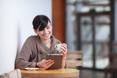 Young woman sitting in the restaurant with digital tablet — Foto de Stock
