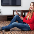 Happy young woman with tablet in living room — Stock Photo