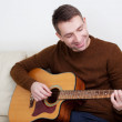 Handsome young man playing guitar — Stock Photo
