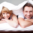 Happy couple lying in bed — Stock Photo