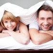 Stock Photo: Happy couple lying in bed