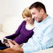 Happy young couple sitting on couch using digital tablet — Stock Photo