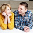 Happy young couple lying on the carpet at home — Stock Photo
