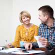Happy young couple paying bills — Stock Photo