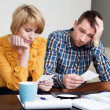 Stock Photo: Sad young couple paying bills.
