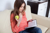 Young woman reading book in living room — Stock Photo