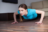 Beautiful young woman doing push-ups at home — Stock Photo