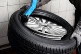 Mechanic changing tyre — Stock Photo