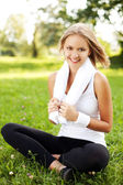 Happy young woman sitting on grass — Stock Photo