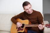 Pohledný mladý muž hraje kytara — Stock fotografie