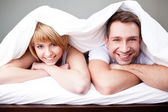 Happy couple lying in bed — Foto Stock