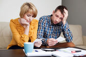 Sad young couple paying bills. — Stock Photo