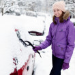 Young woman remove snow from car — Stockfoto