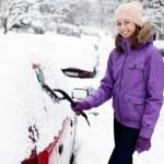 Junge Frau Schnee aus Auto entfernen — Stockfoto