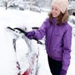 Young woman remove snow from car — Stok fotoğraf