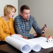 Couple calculating the price of a home — Stock Photo #25791703