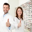 Two happy optician, optometrist showing thumbs up — Stock Photo