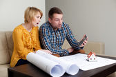 Couple calculating the price of a home — Stock Photo