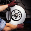 Car mechanic Repairing brakes on car — Stock Photo