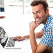 Handsome happy man working with laptop — Stock Photo