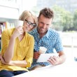 Couple in library working with digital tablet — Stock Photo