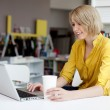 Happy female manager working on laptop in bookshop — Foto Stock