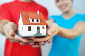 Young couple holding miniatre house — Stock Photo