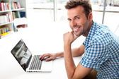Handsome happy man working with laptop — 图库照片