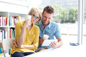 Couple in library working with digital tablet — Foto de Stock