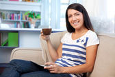 Woman on couch with caffee and digital tablet — Stock Photo