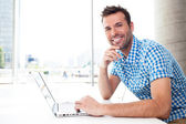 Happy man working with laptop — Stock Photo