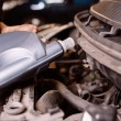 Stock Photo: Car mechanic fills engine oil