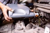 Car mechanic changing engine oil — Stock Photo