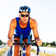 Triathlete cycling on a bicycle — Stock Photo
