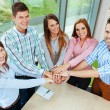 Group of  happy corporate people joining hands over table  — Stock Photo