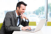 Happy businessman working with laptop — Stock Photo