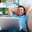 Man relaxing with laptop on couch — Stock Photo
