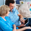 Happy couple on couch using digital tablet — Stock Photo #34453663