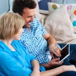 Happy couple on couch using digital tablet — Stock Photo