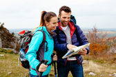 Backpackers with map — Stock Photo