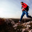 Backpacker jumping on rocks — Stock Photo